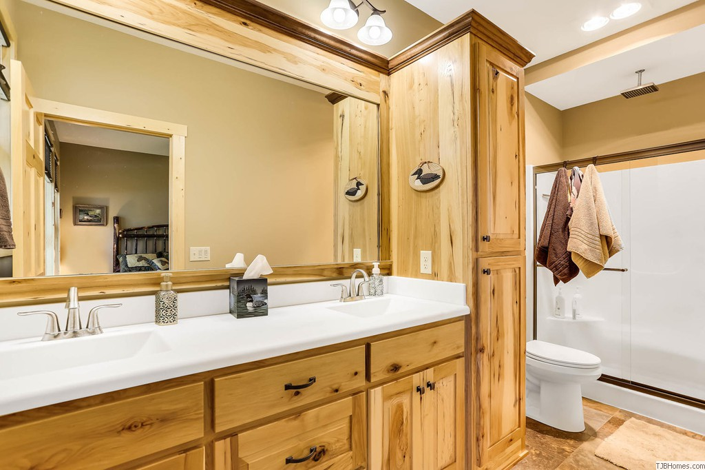 Large master bath with rustic look custom cabinets and rain style showerhead
